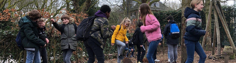 Kinderen zijn aan het spelen op een groenblauw schoolplein. Er staan veel bomen, halfverharding en natuurlijke speelelementen.
